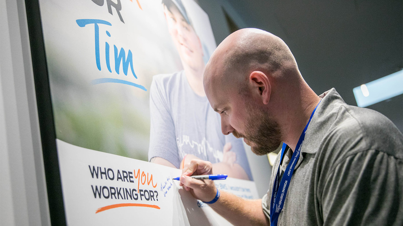 Bristol Myers Squibb invites patient to visit its offices and speak to employees about their health journey. Tim Grimes, part of Global Patient Week 2018, autographs a poster in New Jersey.