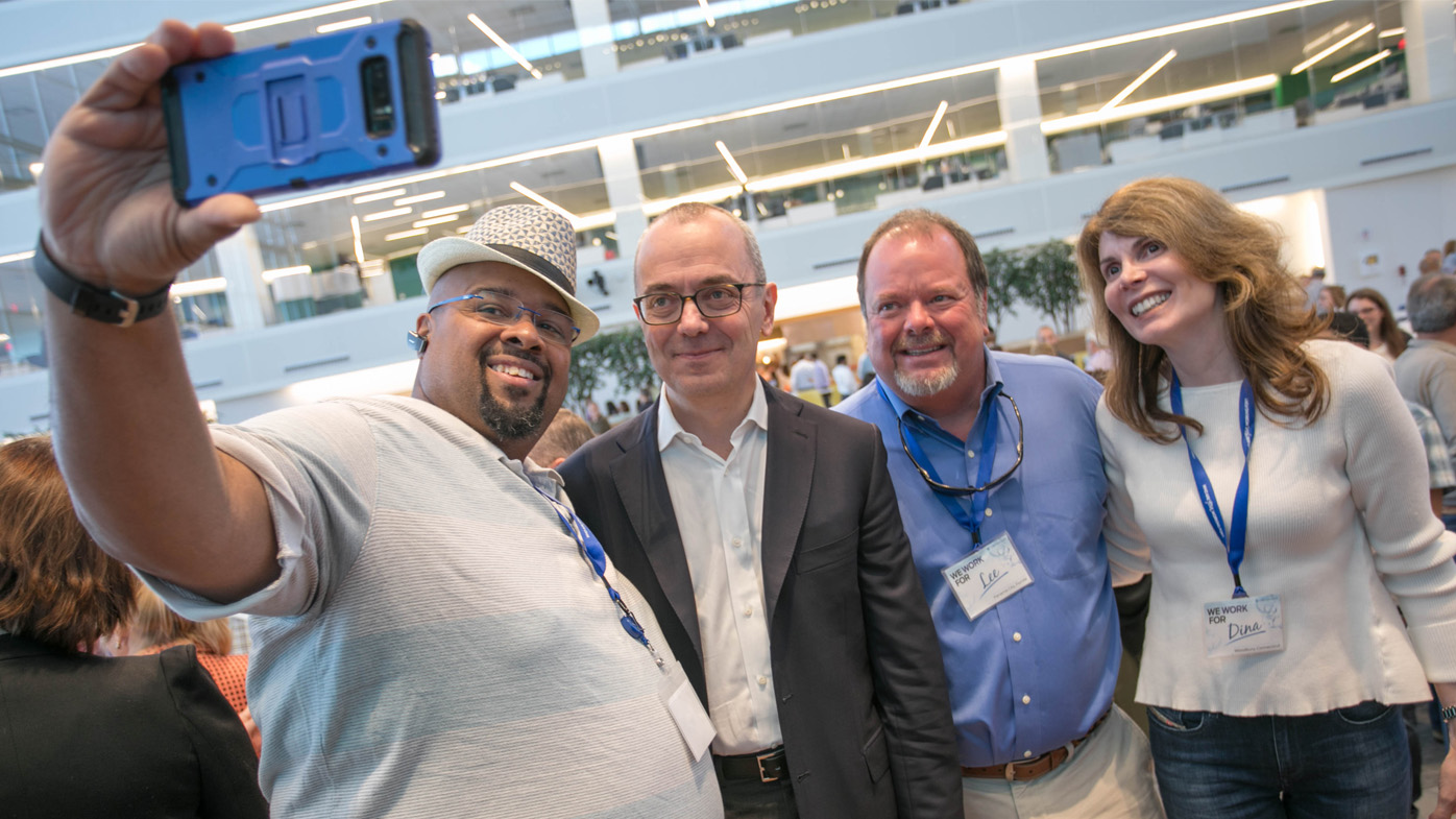 Chairman and CEO Giovanni Caforio, second from left, pictured with Bristol-Myers Squibb patients K.T., Lee and Dina.