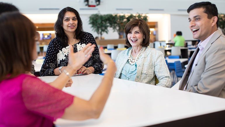 Rita Fawcett (center), of the cardiovascular field team, talks with PAN members, including Manisha Mahimkar (left) and Shalabh Singhal, who helped create training materials that shed light on important cultural insights.