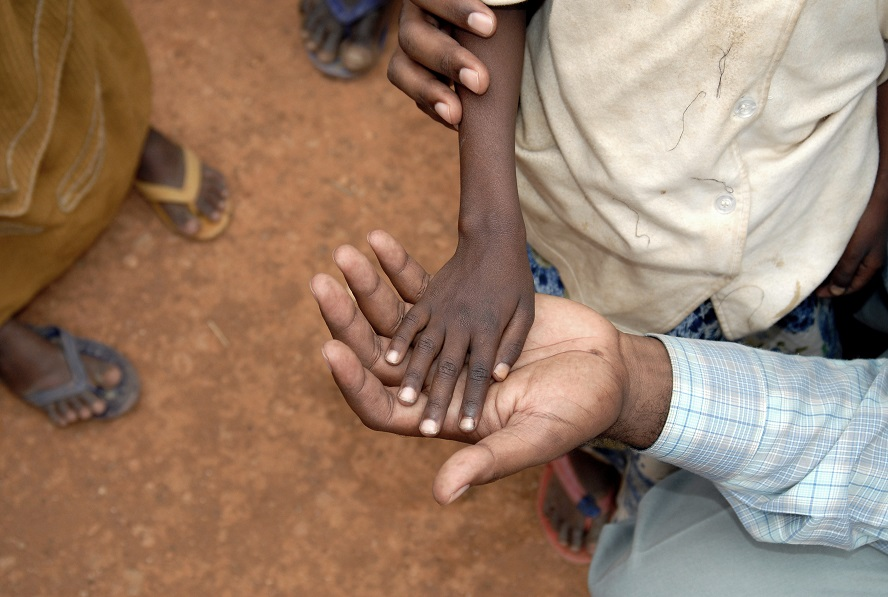 Child's hand on top of doctor's hand