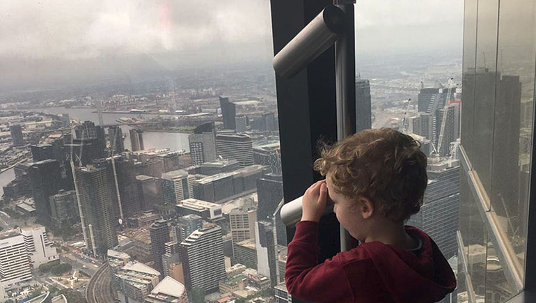 Three-year-old Lowen looks out over the haze of smoke from nearby bushfires shrouding Melbourne.